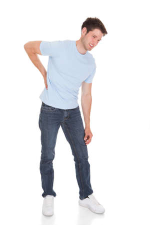 Young Man Suffering From Back Pain Isolated Over White Background Stock Photo - 23183250