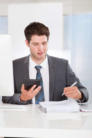 Happy Young Businessman Calculating Bills At Desk photo
