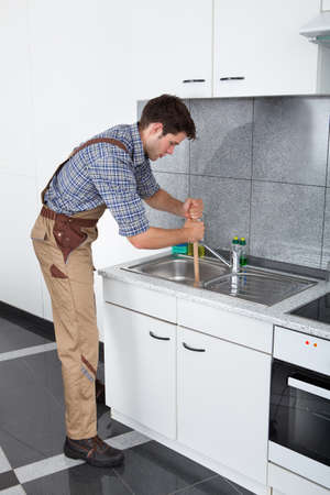 Young Handsome Man Using Plunger In Kitchen Sink photo