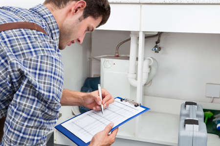 mantenimiento: Guapo fontanero joven escrito en el portapapeles con la pluma en la cocina Sala Foto de archivo