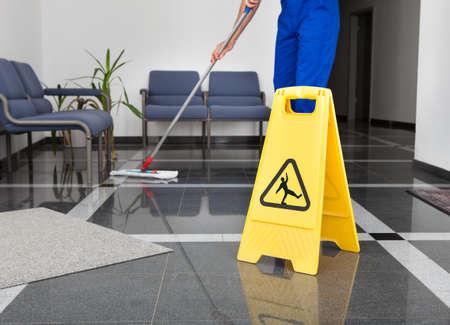 Office uniforms: Primer plano del hombre limpiar el piso con amarillo piso mojado Entrar Foto de archivo