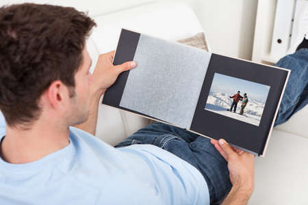 Young Man Sitting On Couch Looking At Photo Album