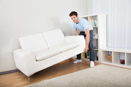 Young Handsome Man Lifting Couch In Living Room photo