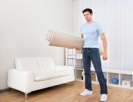 sala parto: Giovane uomo bello che trasportano tappeto arrotolato in Soggiorno