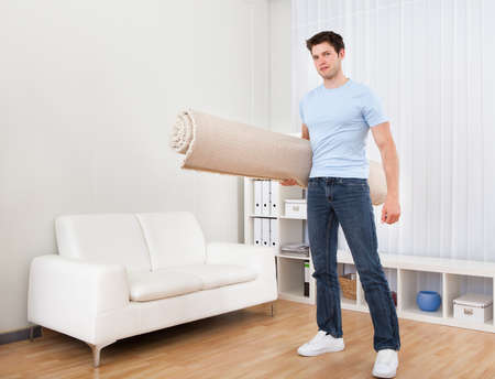 furniture: Young Handsome Man Carrying Rolled Carpet In Living Room