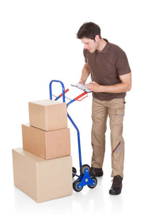 Young Delivery Man Holding Clip Board Standing With Stack Of Boxes photo