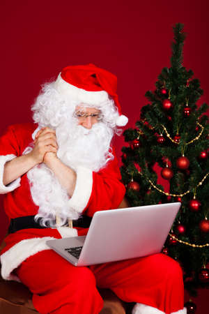 Portrait of santa looking at laptop over white background photo