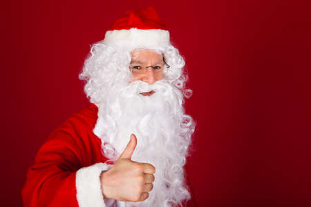 Portrait of happy santa gesturing thumb-up on red background photo