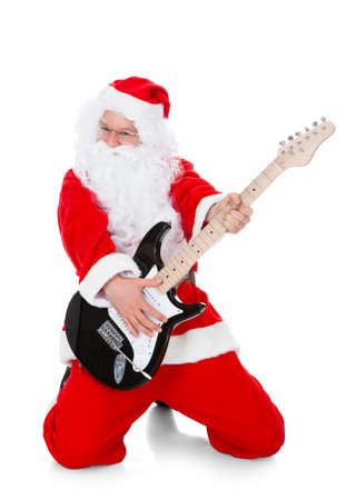 Portrait of a santa playing guitar over white background photo