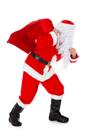 Portrait of santa carrying sack over white background photo