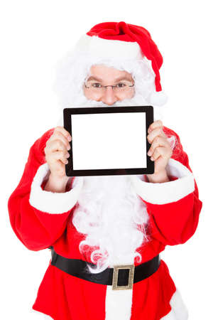 Portrait of santa pointing at digital tablet over white background photo