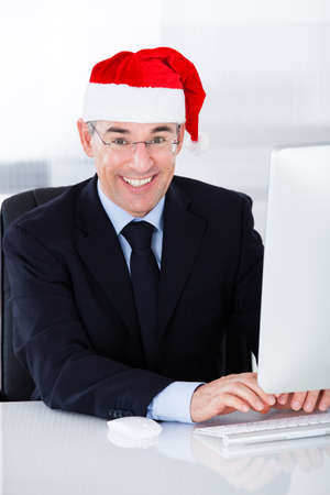 Mature Businessman Wearing Santa Hat Working On Computer In Office photo