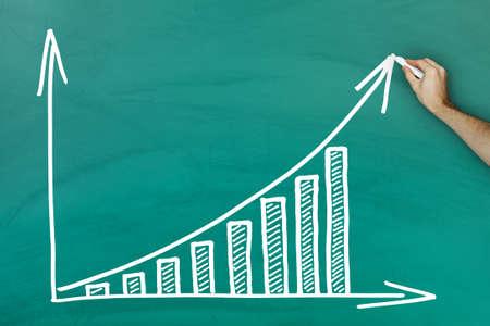 bar: Hand holding chalk writing profit growth chart on green blackboard Stock Photo