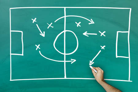 Hand writing football game strategy on green blackboard photo