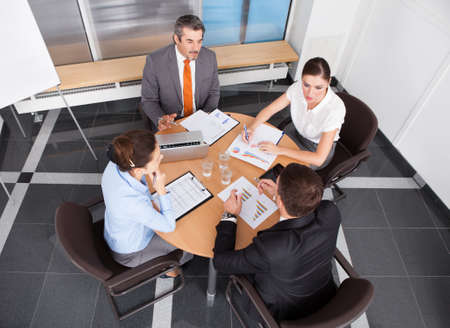 round table conference: Group Of Coworkers Discussing Together In Office Meeting