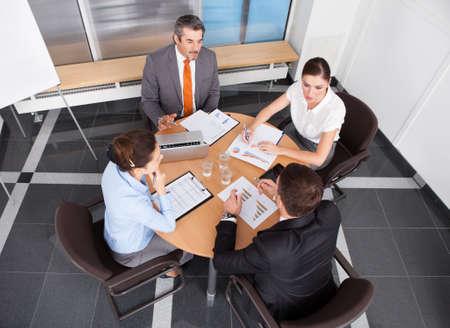 person sitzend: Gruppe von Mitarbeitern diskutieren gemeinsam in Office Meeting