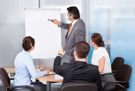 Businessman Giving Presentation To His Colleagues At Conference photo