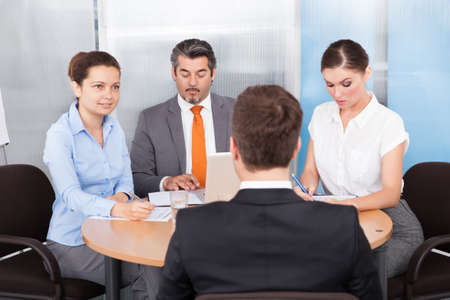 interviewing: Businesspeople Conducting Interview Of A Candidate In The Office