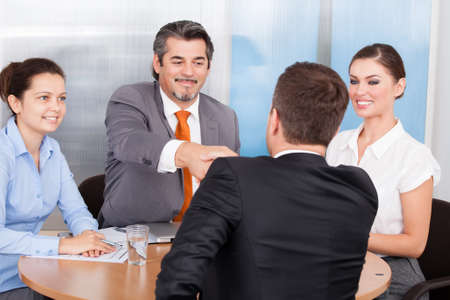 passed: Two Business Partner Shaking Hands In Front Of Colleagues Stock Photo