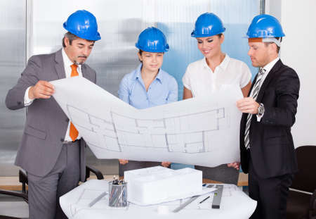 Group Of Architects Wearing Blue Hardhat Looking At Blueprint photo