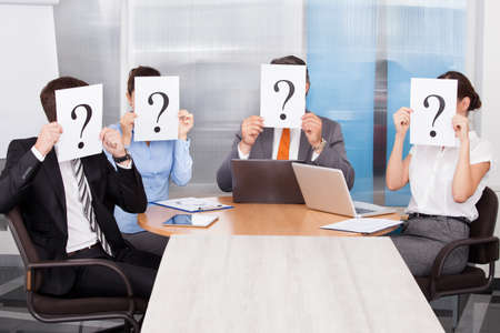 jury: Group Of Businesspeople Sitting In A Conference Room Holding Question Mark Sign Stock Photo