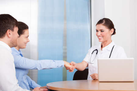 Happy Young Couple Shaking Hands With Female Doctor At Clinic photo