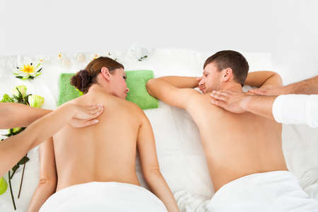 Young Couple Relaxing And Enjoying A Joint Back Massage At A Spa photo