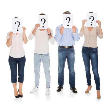 自分の顔の前に疑問符記号を保持している人々 のグループ