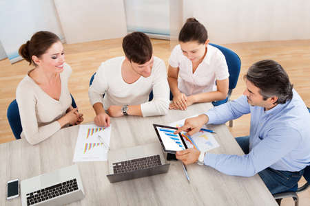 Business Executives At A Meeting Discussing Work On Digital Tablet photo