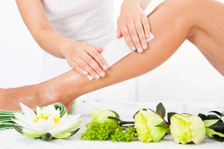 leg: Beautician Waxing A Womans Leg In Spa Stock Photo