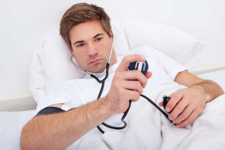 own blood: Man Lying On Bed Checking His Own Blood Pressure
