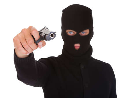 Portrait Of A Burglar With Balaclava Holding Hand Gun Isolated On White Background photo