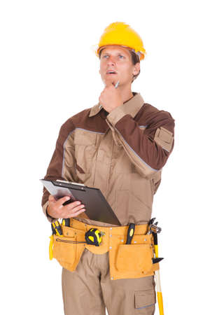 Happy Young Mechanic In Protective Workwear Writing On Clipboard photo