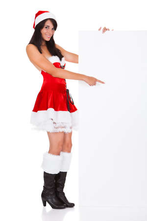 Young Woman Wearing Santa Clause Costume Holding Blank Placard Over White Background photo