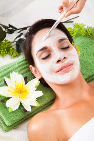 chemical peels: Cosmetician Applying Facial Beauty Mask For Young Woman At Spa Salon Stock Photo