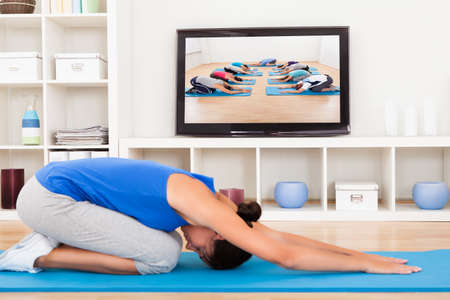 Female Doing Fitness Exercise In Front Of Television photo