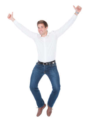 Happy Young Man Showing Thumb Up Over White Background photo