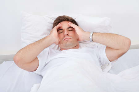 Portrait Of A Young Man Lying On Bed Suffering From Headache photo