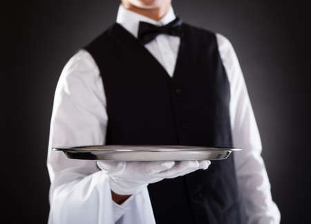 Portrait Of A Male Waiter Holding Tray Over Black Background photo