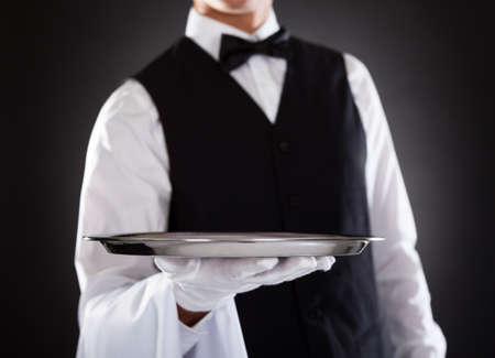 camarero: Retrato de un camarero de sexo masculino que sostiene la bandeja Sobre Fondo Negro Foto de archivo