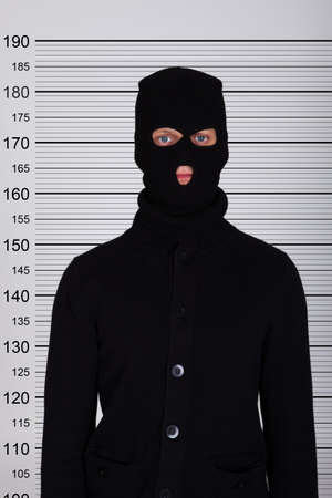 Burglar Wearing Balaclava Standing Against Police Lineup photo