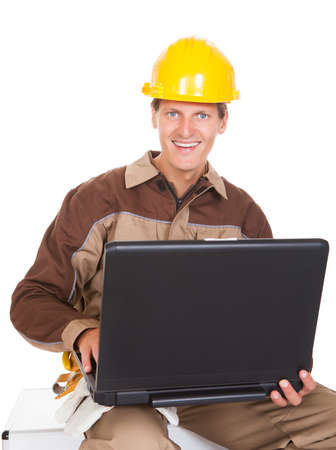 Happy Young Mechanic In Protective Workwear Holding Laptop photo