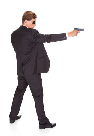 Young Man In Black Suit Aiming With A Gun On White Background photo