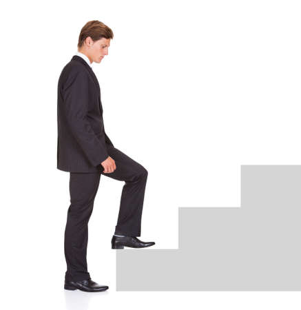Young Businessman Started Climbing Step Of Success On White Background photo