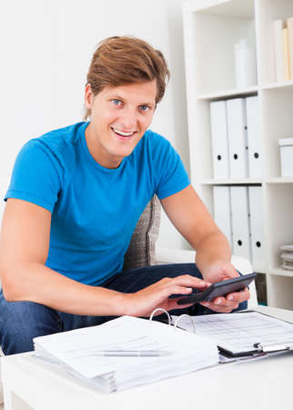 taxes budgeting: Portrait Of A Young Man At Home Calculator His Finance Expenses