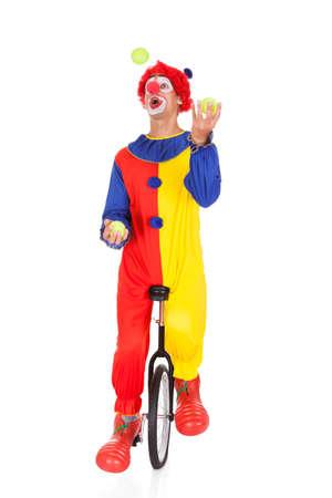 payaso: Retrato de un payaso que hace juegos malabares con las bolas en monociclo Sobre Fondo Blanco