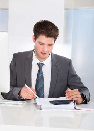 Happy Young Businessman Calculating Bills At Desk photo