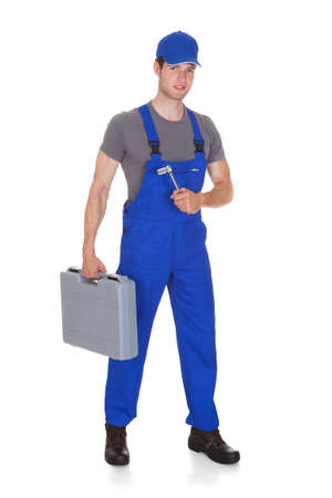 studio happy overall: Male Mechanic Holding Ratchet And Toolbox On White Background Stock Photo