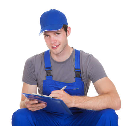 Young Construction Worker Writing On Clipboard Over White Background photo
