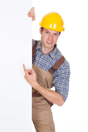 Worker Wearing Hardhat And Holding Blank Placard Isolated On White Background photo